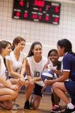 Женская команда волейбола средней школы имеет беседу команды от тренера Стоковая Фотография RF