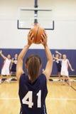Женская корзина стрельбы баскетболиста средней школы Стоковые Фотографии RF