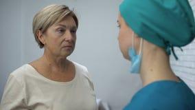 Женская медсестра говоря терпеливый плохой диагноз, разочаровывая новости, плакать женщины сток-видео