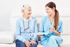 Женская медсестра дает старшему лекарству лекарство стоковое фото