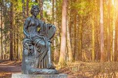 Женская медная статуя божества с арфой в древесинах Стоковое Изображение
