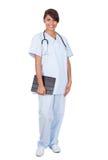 Женская медсестра держа цифровую таблетку против белой предпосылки Стоковые Фото