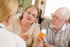 Женская медсестра объясняя медицину рецепта к старшему Coupl Стоковые Фото