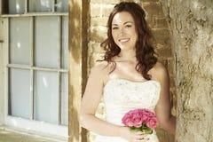 Женская невеста стоя против солнечной стены и дерева Стоковые Изображения RF