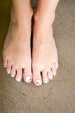 Женская нога с красивым Pedicure на песке Стоковое фото RF