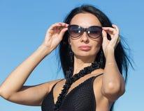 Женская персона в цельном купальнике регулируя солнечные очки стоковое изображение