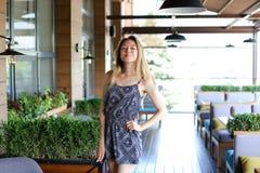 Женская персона стоя на кафе около зеленых palnts Стоковое фото RF