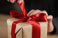 Женская предназначенная для подростков рука идя развязать смычку на подарочной коробке Стоковые Изображения
