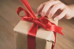 Женская предназначенная для подростков рука идя развязать смычку на подарочной коробке Стоковые Изображения RF
