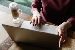 Женская работа на компьтер-книжке в кафе домашняя компьтер-книжка используя женщину Используя интернет компьтер-книжки рука испол Стоковое Изображение RF