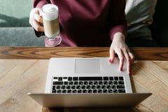 Женская работа на компьтер-книжке в кафе домашняя компьтер-книжка используя женщину Используя интернет компьтер-книжки рука испол Стоковая Фотография