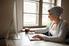 Женская работа на компьютере и выпивая кофе Стоковое Изображение RF