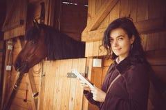 Женская работа на цифровой таблетке рядом с конюшней лошади Стоковые Изображения
