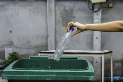 Женская рука бросая пустую пластичную бутылку в погань Стоковые Изображения RF