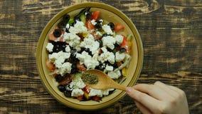 Женская рука брызгает приправу от деревянной ложки на вегетарианском низко- салате грека калории Конец-вверх взгляд сверху сток-видео