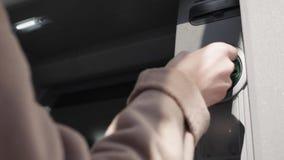 Женская рука вводит дебетовую карту в ATM видеоматериал