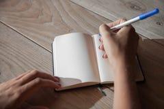 Женская рука делая примечания в тетради стоковое фото rf