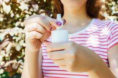 Женская рука держа брызг бутылки носовой в парке Стоковое Фото