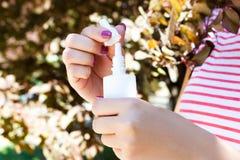 Женская рука держа брызг бутылки носовой в парке Стоковая Фотография RF