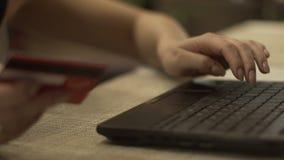 Женская рука держа карточку банка и печатая на клавиатуре тетради для онлайн оплаты акции видеоматериалы