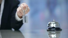Женская рука держа ключи гостиничного номера около колокола на приеме, обслуживания гостеприимства сток-видео