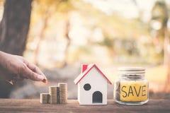 Женская рука держа монетки на стеклянном опарнике с домом слова и модели спасения на таблице в предпосылке bokeh природы Стоковые Фотографии RF