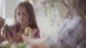 Женская рука держа пасхальное яйцо пока меньшая усмехаясь картина девушки на ей сердце с концом небольшой щетки вверх Подготовка видеоматериал