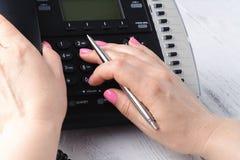 Женская рука держа приемник телефона и набирая номер стоковое изображение