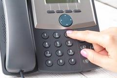 Женская рука держа приемник телефона и набирая номер стоковая фотография