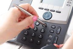 Женская рука держа приемник телефона и набирая номер стоковая фотография rf