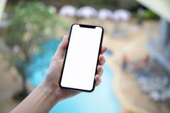 Женская рука держа телефон с изолированным бассейном h предпосылки экрана Стоковые Фото
