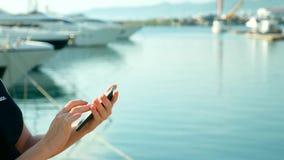 Женская рука держит смартфон на запачканной предпосылке порта с яхтами сток-видео