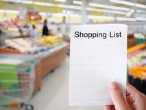 Женская рука держа бумагу списка покупок на ба нерезкости гастронома Стоковое Фото