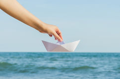 Женская рука держа бумажную шлюпку на предпосылке моря Стоковые Фото