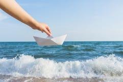 Женская рука держа бумажную шлюпку на предпосылке моря Стоковая Фотография RF