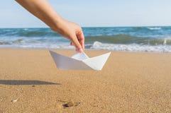 Женская рука держа бумажную шлюпку на предпосылке моря Стоковое Изображение