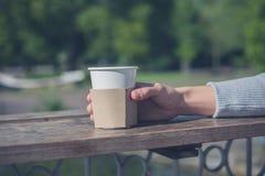 Женская рука держа бумажный стаканчик стоковые изображения rf