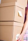 Женская рука держа кучу коричневых картонных коробок Стоковая Фотография