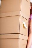 Женская рука держа кучу коричневых картонных коробок Стоковые Изображения