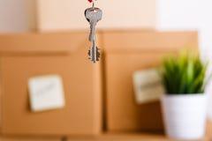 Женская рука держа ключи над кучей коричневых картонных коробок Стоковые Фото