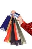 Женская рука держа много хозяйственных сумок и кредитную карточку. Стоковая Фотография