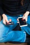 Женская рука держа пластичную кредитную карточку и используя smartphone Стоковые Фото