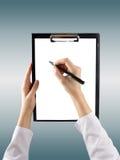 Женская рука держа ручку и доску сзажимом для бумаги с чистым листом бумаги (docu Стоковые Фотографии RF