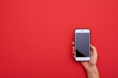 Женская рука держа экран белого умного телефона пустой над задней частью красного цвета стоковое фото rf