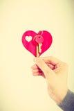 Женская рука держит меньшее сердце с ключами стоковая фотография