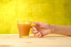 Женская рука держит сок персика в стекле Стоковые Изображения RF