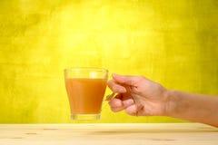 Женская рука держит сок персика в стекле Стоковое Изображение RF
