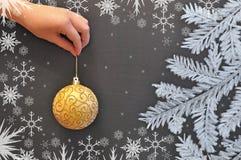 Женская рука держит шарик рождества на фоне доски стоковые изображения rf