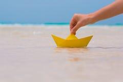 Женская рука играя с бумажной шлюпкой в воде на пляже Стоковые Фото