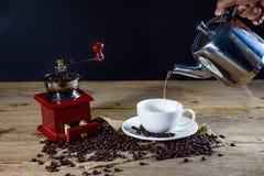 Женская рука лить горячую воду в кофейную чашку стоковое изображение